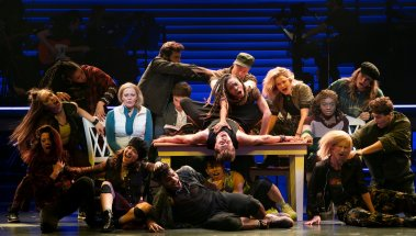 "Elizabeth Stanley, seated near table at left, and Celia Rose Gooding, seated at right, with the ensemble of ""Jagged Little Pill."" Photo by Sara Krulwich/The New York Times"